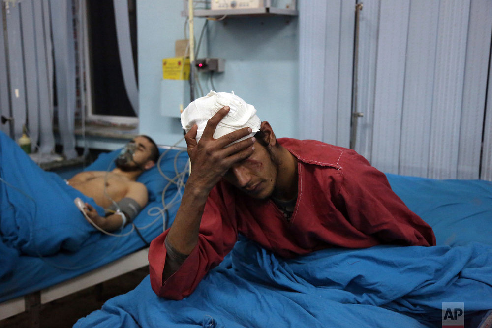 Injured men receive treatment at a hospital after a suicide bombing in Kabul, Afghanistan, Nov. 20, 2018. (AP Photo/Rahmat Gul)