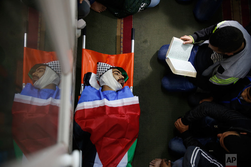 Palestinians pray by the body of Mohammed Habali 22, during his funeral in the Tulkarem refugee camp near the West Bank city of Tulkarem, Dec. 4, 2018. (AP Photo/Majdi Mohammed)