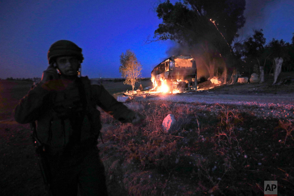 An Israeli soldier stands near a burning bus after it was hit by a mortar shell fired from Gaza near the Israel Gaza border, Nov. 12, 2018. (AP Photo/Tsafrir Abayov)
