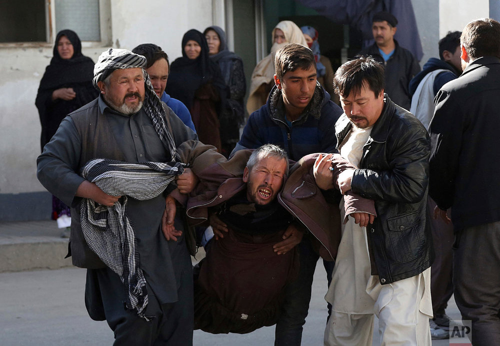 A distraught man is carried following a suicide attack in Kabul, Afghanistan, Dec. 28, 2017. Authorities say attackers stormed the Shiite Muslim cultural center in the Afghan capital Kabul, setting off multiple bombs and killing dozens. (AP Photo/Rahmat Gul)