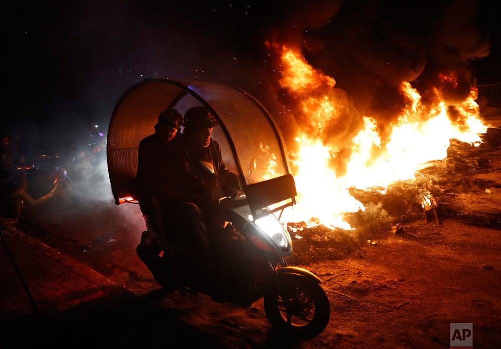 Supporters of Lebanese Parliament Speaker Nabih Berri ride a scooter past a road block, during a protest against Lebanese Foreign Minister Gibran Bassil, in Beirut, Lebanon, Jan. 29, 2018. (AP Photo/Hussein Malla)