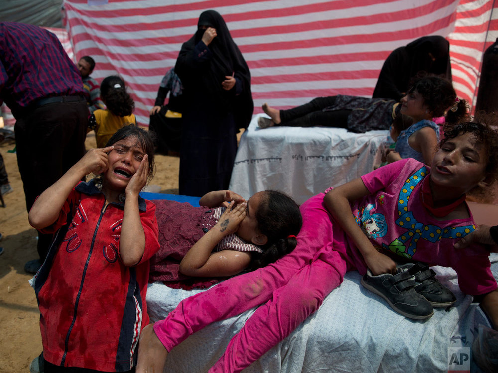 Palestinian children suffering from teargas inhalation recover in a medical tent during a protest near Beit Lahiya, Gaza Strip, May 14, 2018. (AP Photo/Dusan Vranic)