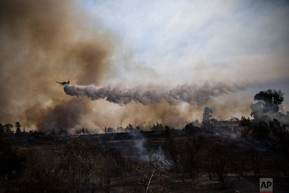 A firefighting plane passes over a fire started by a balloon with attached burning cloth launched by Palestinians from Gaza Strip in Karmia nature reserve park near the Israel and Gaza border, Oct. 11, 2018. (AP Photo/Tsafrir Abayov)