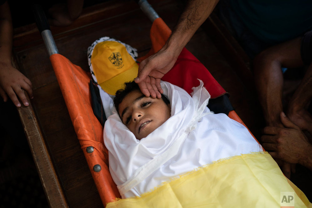 """Palestinians mourn over the body of 11-year-old Shady Abdel-al during his funeral in Beit Lahiya, northern Gaza Strip Sept. 15, 2018. Though the Health Ministry initially reported Abdel-al was shot by Israeli fire, the Israeli army claimed he was accidentally struck by a rock thrown by protesters. Two Gaza rights groups say he died after being hit """"with a solid object."""" (AP Photo/Felipe Dana)"""