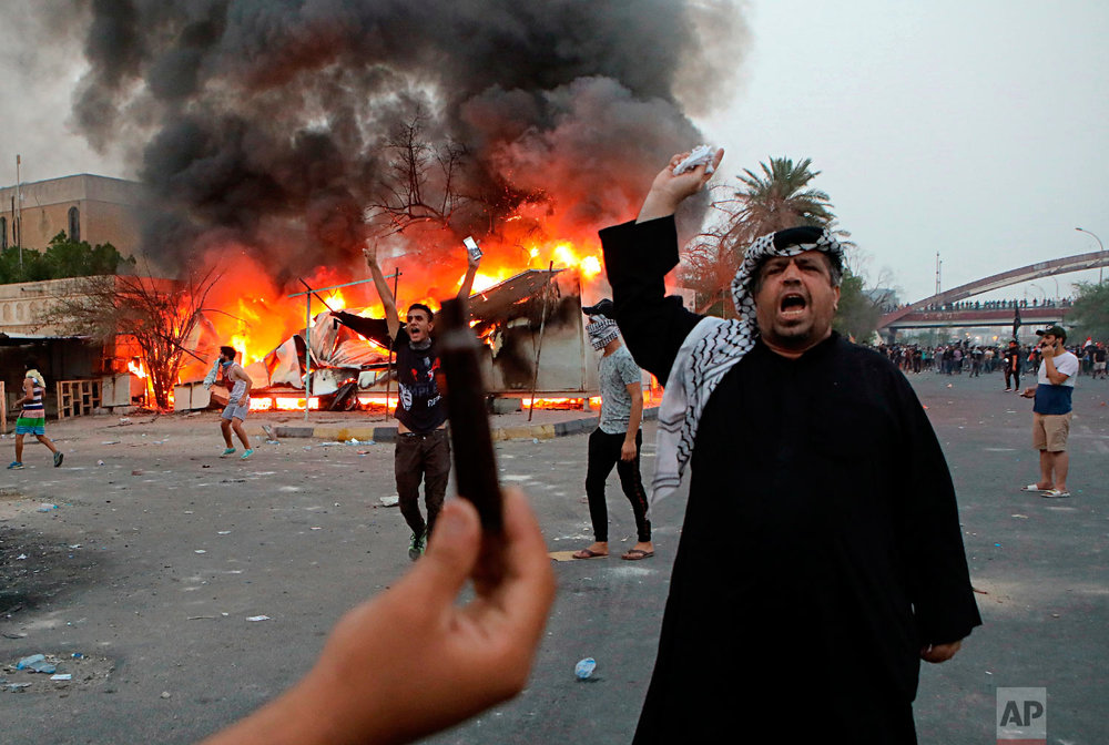 Protesters try to storm and burn the governor's building during protests demanding better public services and jobs, Tuesday, Sept. 4, 2018, in Basra, 340 miles (550 kilometers) southeast of Baghdad, Iraq.  (AP Photo/Nabil al-Jurani)