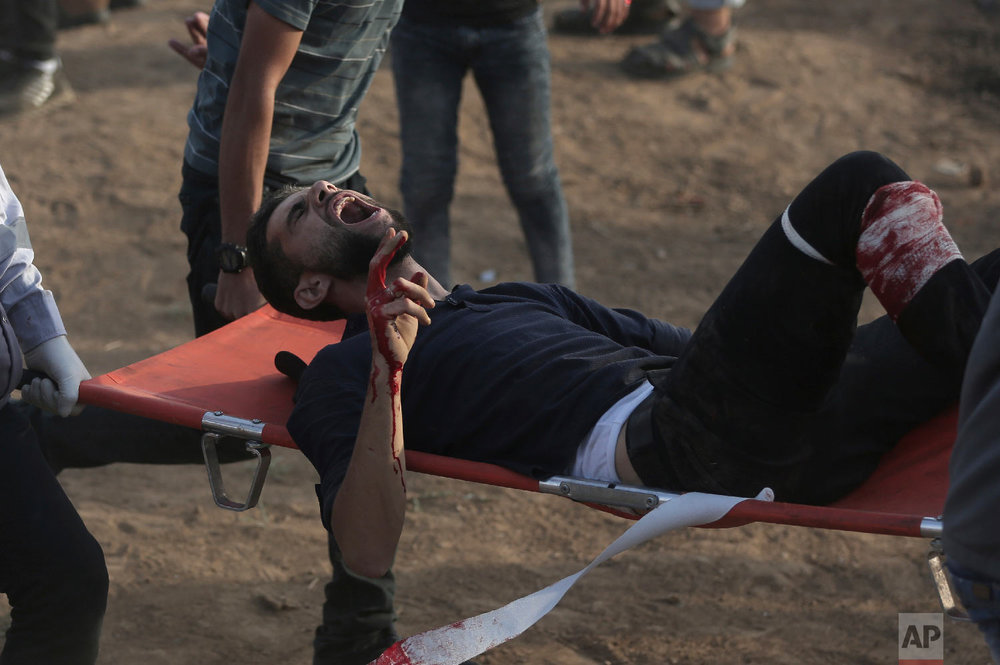 Palestinian medics carry a wounded protester during a protest at the Gaza Strip's border with Israel, Oct. 5, 2018. (AP Photo/Khalil Hamra)