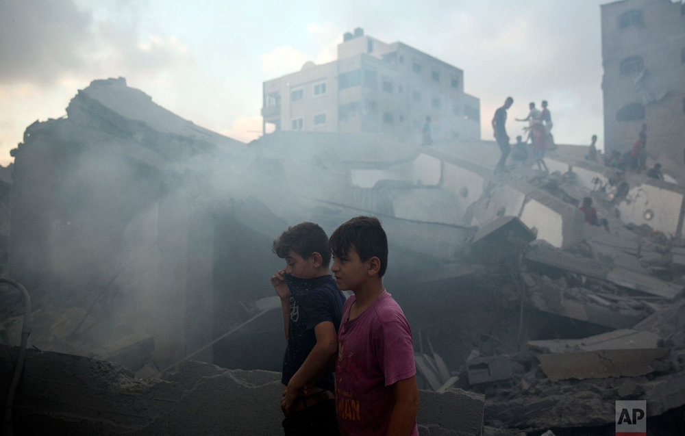 Palestinians inspect the damaged building of Said al-Mis'hal cultural center after it was hit bombed by an Israeli airstrike in Gaza City, Thursday, Aug. 9, 2018. (AP Photo/Khalil Hamra)