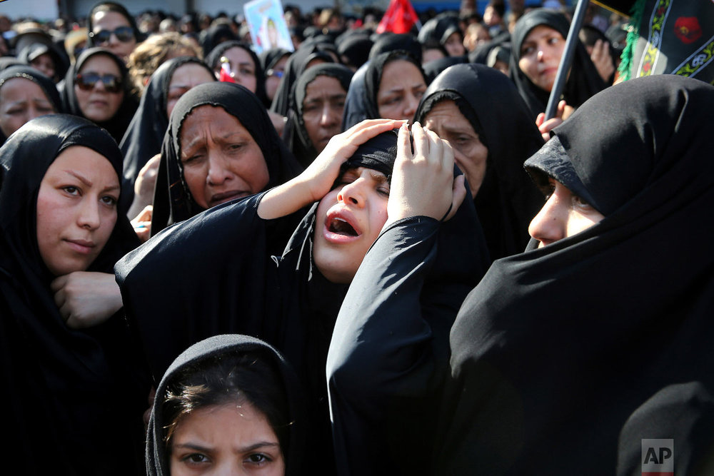 Families of victims of a terror attack on a military parade in the southwestern city of Ahvaz, that killed 25 people attend a mass funeral ceremony, in Ahvaz, Iran, Sept. 24, 2018. (AP Photo/Ebrahim Noroozi)
