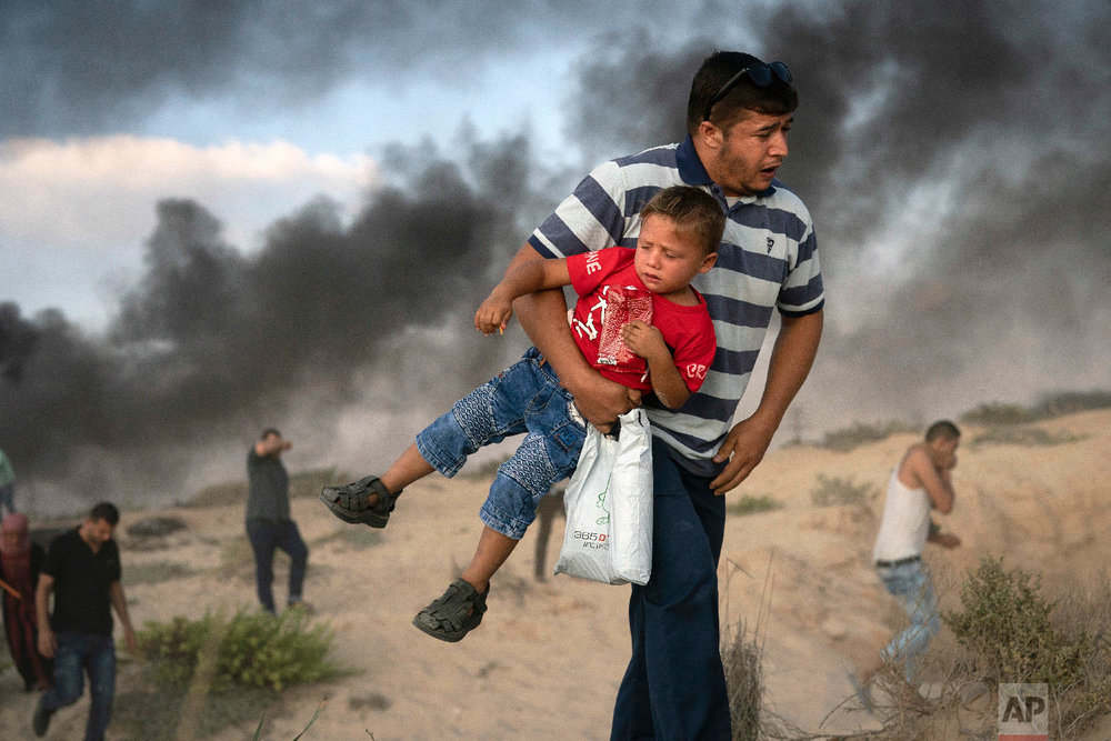 A Palestinian protester carries a boy as he runs from tear gas fired by Israeli soldiers during a protest on the beach near the border with Israel in Beit Lahiya, northern Gaza Strip, Sept. 10, 2018. (AP Photo/Felipe Dana)