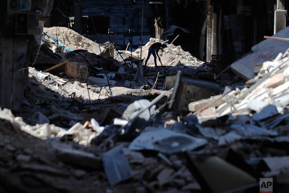 A young man removes rubble in front of his shop in the Palestinian refugee camp of Yarmouk in the Syrian capital Damascus, Syria, July 16, 2018. (AP Photo/Hassan Ammar)