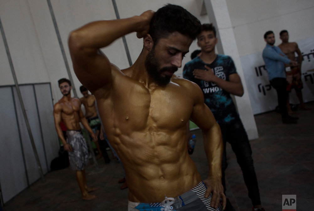 APalestinian bodybuilder prepares himself before giving a performance during a local bodybuilding competition, in Gaza City, Oct. 26, 2018. (AP Photo/Khalil Hamra)