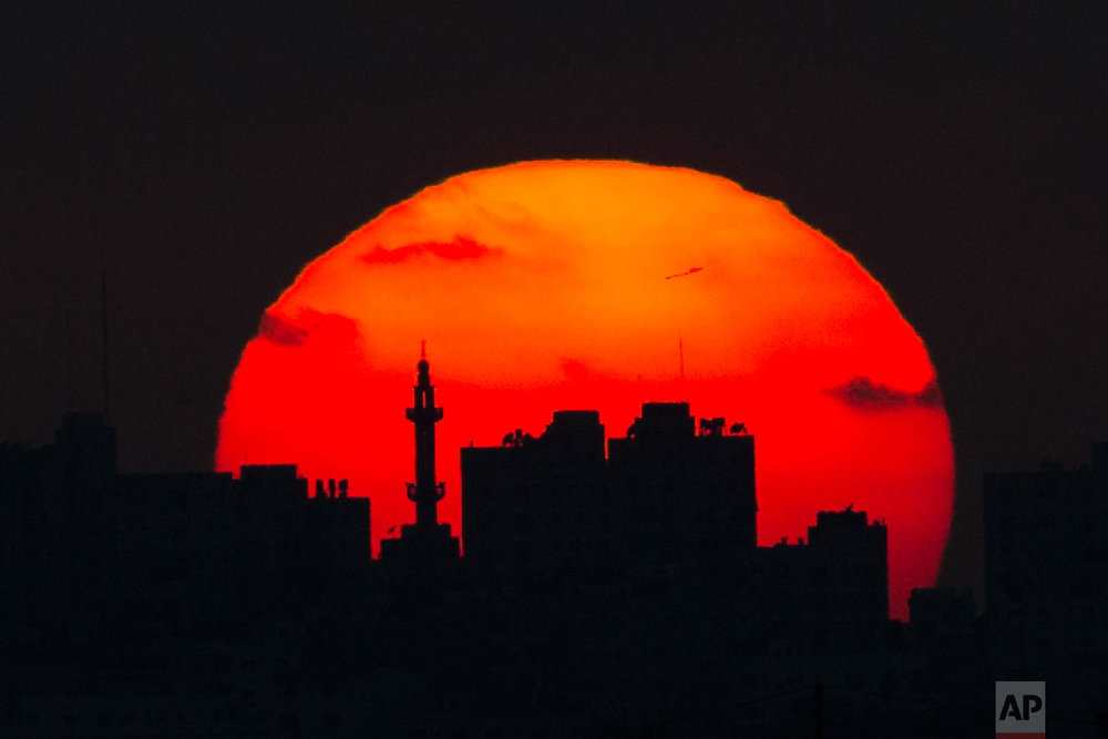 The sun sets behind a mosque and buildings in the Gaza Strip, May 15, 2018. (AP Photo/Ariel Schalit)
