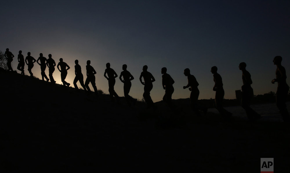 Palestinian students march during sunset in a display of their military skills at Al-Rebat College for Law and Police Science in Khan Younis, southern Gaza Strip, Sept. 23, 2018. (AP Photo/Adel Hana)