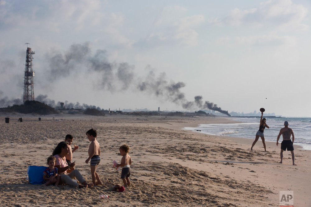 Israelis enjoy the day in Zikim beach, near kibbutz Zikim, on the Israel and Gaza border, as in the background black smoke rises from the tires set on fire by Palestinian protesters near Beit Lahiya, northern Gaza Strip, Oct. 8, 2018. (AP Photo/Oded Balilty)