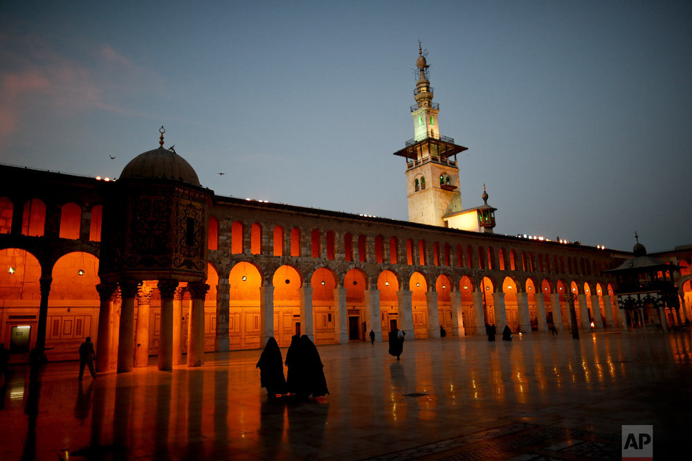 Muslim women walk in the courtyard of the 7th century Umayyad Mosque in Damascus, Syria, Oct. 3, 2018. (AP Photo/Hassan Ammar)