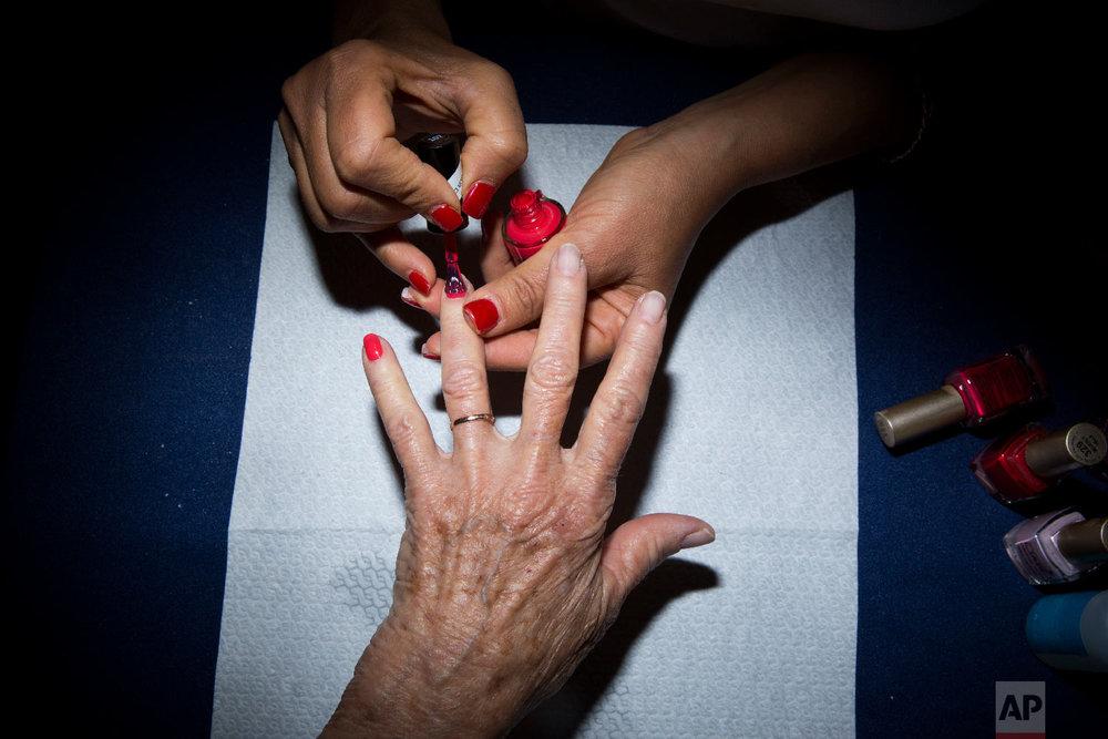 Holocaust survivor Hannah Beker, 79, has fingernail polish applied during a Beauty Heroines event in Ramat Gan, Israel, April 9, 2018. (AP Photo/Oded Balilty)