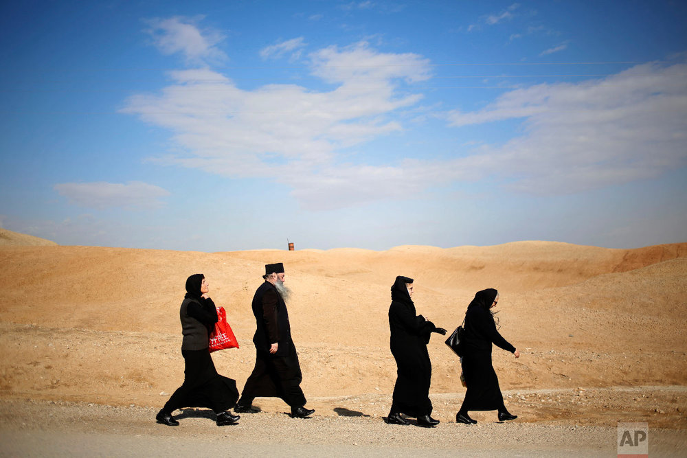 Christians walk to the traditional Epiphany baptism ceremony at the Qasr-el Yahud baptism site, in the Jordan river near the West Bank town of Jericho, Jan. 18, 2018. (AP Photo/Ariel Schalit)