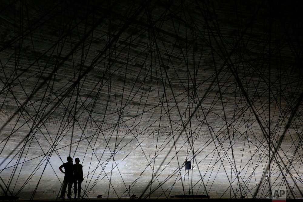 Visitors tour The Experimental Theater, designed in the early 1960s by the late Brazilian architect Oscar Niemeyer, at the Rashid Karami International Fair, in the northern city of Tripoli, Lebanon, Oct. 20, 2018. (AP Photo/Hassan Ammar)