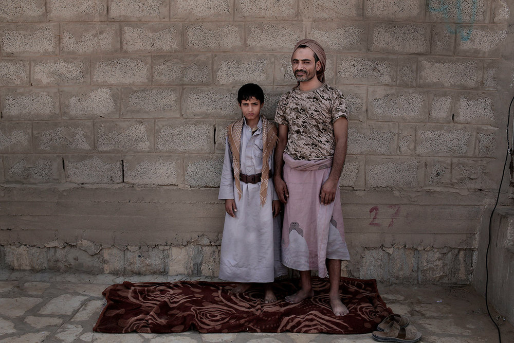 In this July 27, 2018 photo, 14 year-old Abdel Hamid Saleh, and his father pose for a photograph at a camp for displaced persons where they took shelter, in Marib, Yemen, (AP Photo/Nariman El-Mofty)