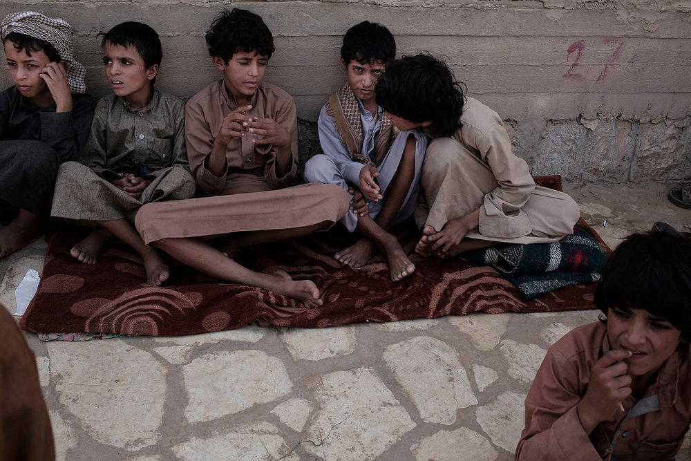 In this July 27, 2018 photo, 14 year-old Abdel Hamid Saleh, second right, and 14 year-old Morsal Al Amery, third right, sit at a camp for displaced persons where they took shelter, in Marib, Yemen, (AP Photo/Nariman El-Mofty)