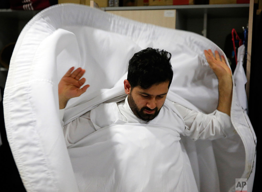 A whirling dervish of the Mevlevi order gets dressed in the locker room prior to a Sheb-i Arus ceremony in Konya, central Turkey, Sunday, Dec. 16, 2018. (AP Photo/Lefteris Pitarakis)