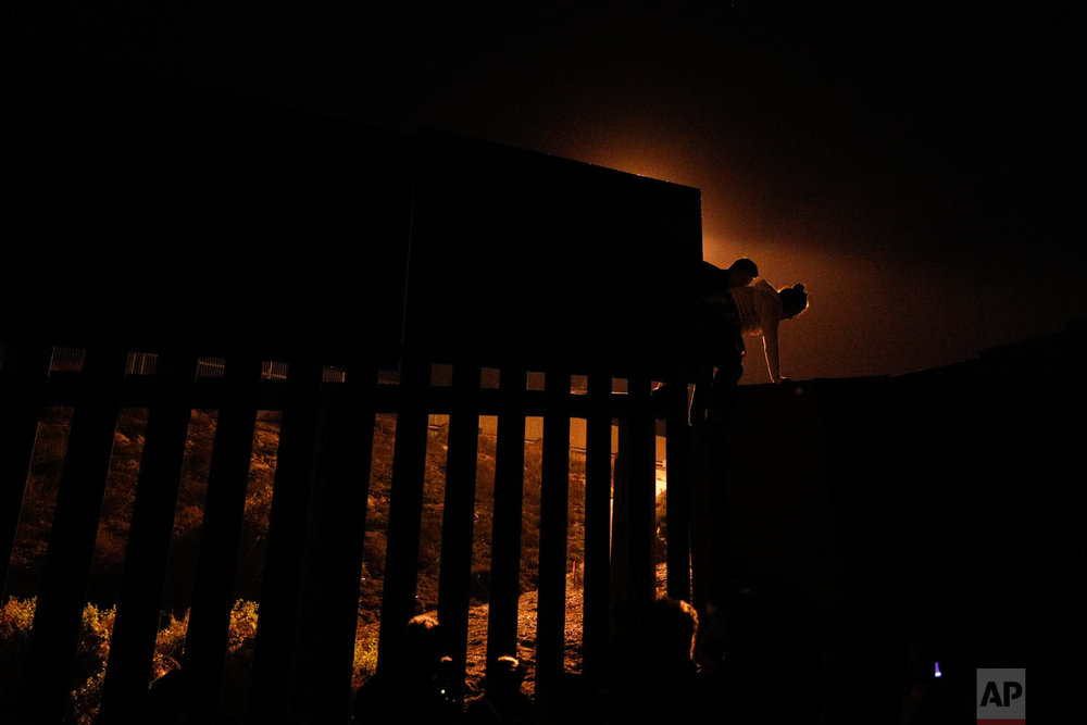 "In this Dec. 2, 2018 photo, Honduran migrants climb over the U.S. border fence before handing themselves in to border control agents in order to apply for asylum, seen from Playas of Tijuana, Mexico. Often within minutes, border officers quickly arrive to escort them to detention centers and begin ""credible fear"" interviews. (AP Photo/Rebecca Blackwell)"