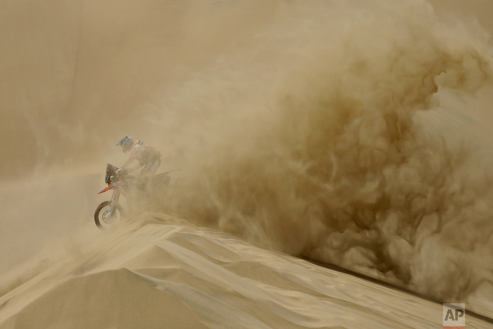 In this Jan. 6, 2018 photo, U.S. athlete Ricky Brabec races his Honda motorbike during the Dakar Rally between Lima and Pisco, Peru. This year's grueling Dakar Rally began on Peruvian sand dunes, took to the highlands of Bolivia and finished in Argentina. (AP Photo/Ricardo Mazalan)