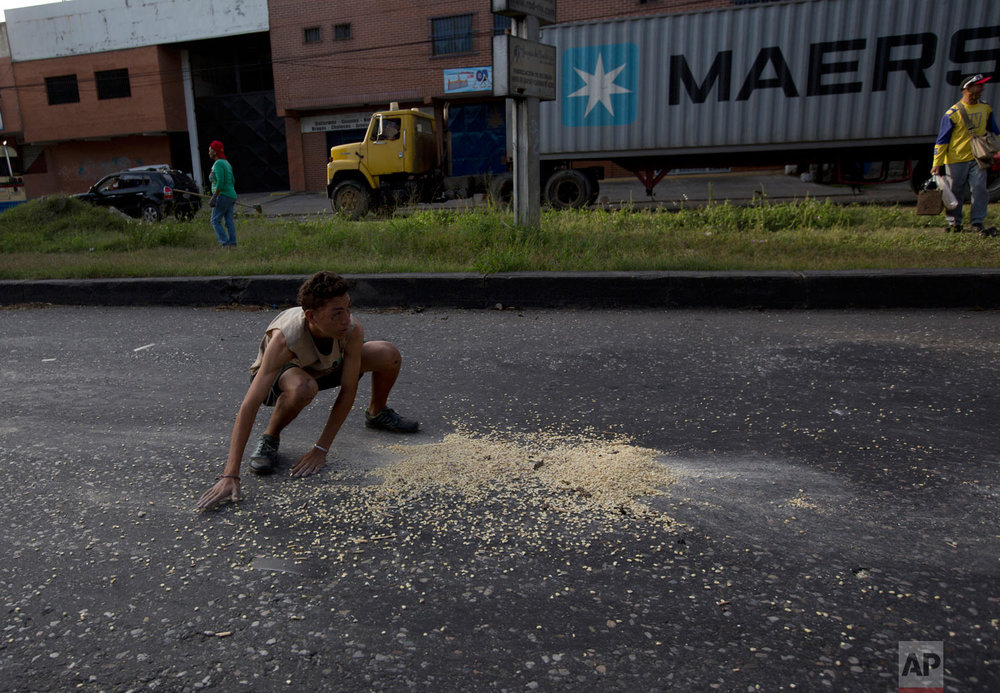 In this Jan. 23, 2018 photo, a youth moves quickly to scoop up grains of corn that fell from a truck while it was looted, just outside the port area of Puerto Cabello, Venezuela. At the country's biggest port, people swarmed the corn-carrying truck and began filling up sacks with the grain while the driver was held at gunpoint, amid the worst economic crisis anybody in Latin America can remember. (AP Photo/Fernando Llano)