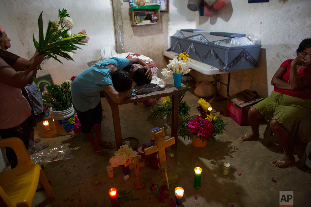 "In this Feb. 8, 2018 photo, Maribel Julio Meneses weeps over the body of her son Daniel Julio Julio, a 22-year-old ""community police"" vigilante who was ambushed and killed while on duty, in the village of Huamuchapa, near Tecoanapa in Guerrero state, Mexico. Fed up with police corruption and drug gang violence, a number of communities have formed citizen police groups. (AP Photo/Rebecca Blackwell)"
