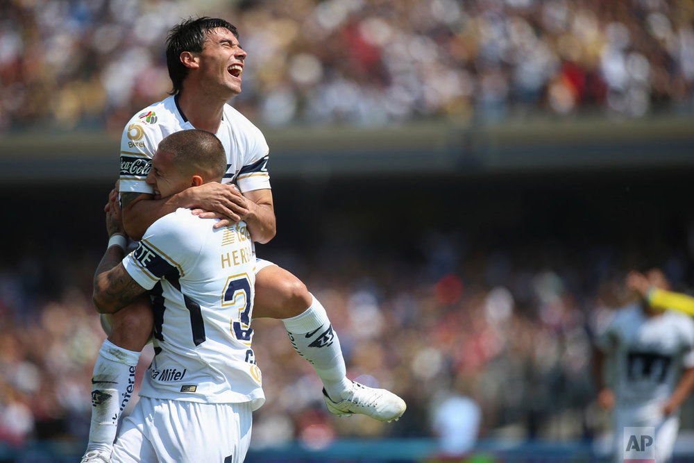 In this Feb. 25, 2018 photo, Pumas' Nicolas Castillo celebrates his goal against Guadalajara as he holds up his teammate Matias Alustiza during a Mexico soccer league match in Mexico City. (AP Photo/Anthony Vazquez)