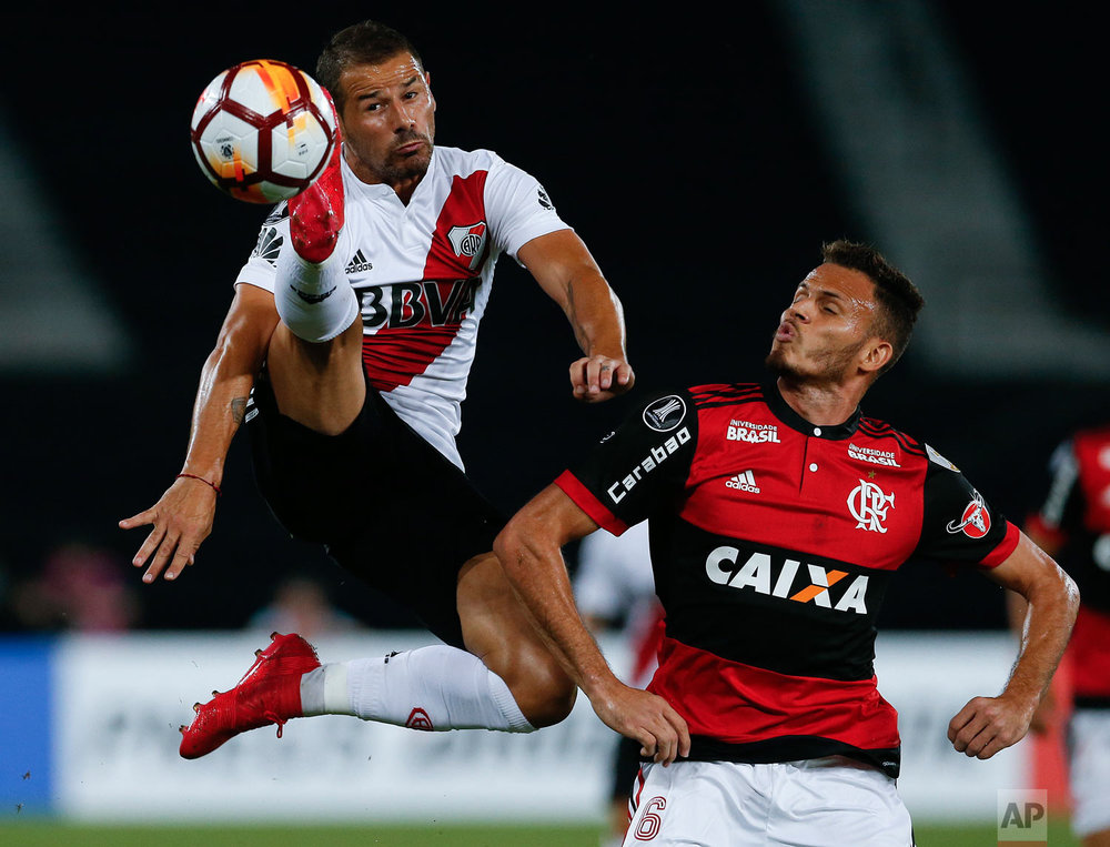 In this Feb. 28, 2018 photo, Rodrigo Mora of Argentina's River Plate kicks the ball as Rene of Brazil's Flamengo looks on during their Copa Libertadores soccer match in Rio de Janeiro, Brazil. (AP Photo/Leo Correa)