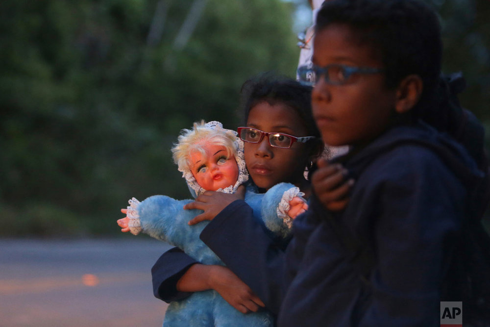 In this March 9, 2018 photo, 9-year-old Ashley Angelina holds her doll as she hitch-hikes with her twin brother Angel David and parents after crossing the Venezuelan border in their migration to Brazil, near Pacaraima. Hungry and destitute, tens of thousands of victims of Venezuela's unrelenting political and economic crisis tried their luck in Brazil. (AP Photo/Eraldo Peres)