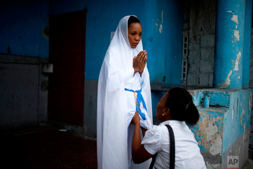 In this March 30, 2018 photo, a woman dressed as the Virgin May holds her hands in prayer as a seamstress puts on the finishing touches to her costume in Port-au-Prince, Haiti. Christian Haitians commemorated the crucifixion of Jesus Christ by reenacting the Way of the Cross, visiting the 14 stations, each marking an event that befell Jesus Christ on his final journey. (AP Photo/Dieu Nalio Chery)