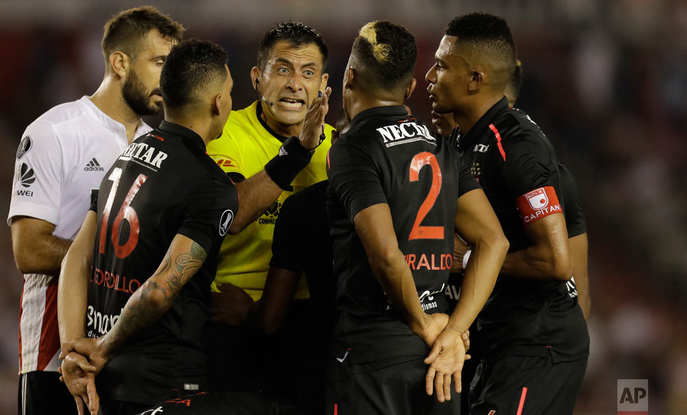 In this April 5, 2018 photo, Chilean referee Luis Bascunan yells at Colombia's Independiente Santa Fe players during a Copa Libertadores soccer match against Argentina's River Plate in Buenos Aires, Argentina. (AP Photo/Natacha Pisarenko)