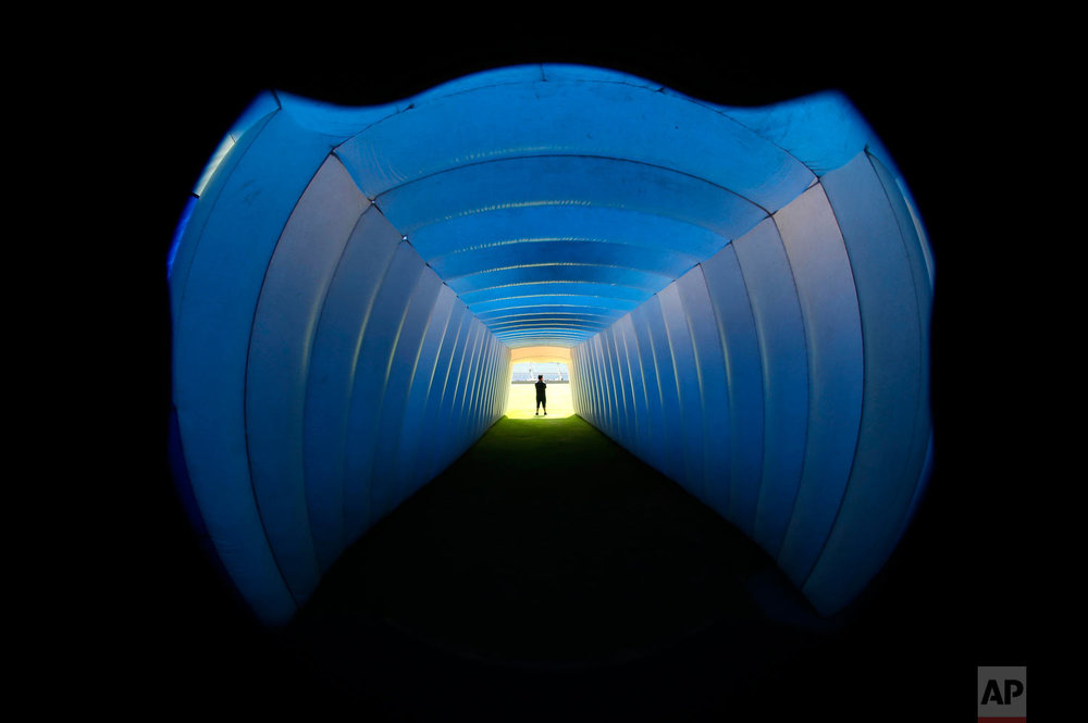 In this April 21, 2018 photo, an inflatable tunnel is illuminated blue before Cruz Azul players go to the field for their Mexico league soccer match with Morelia in Mexico City. This was the last match Cruz Azul played at their home stadium, inaugurated in 1946, before it was demolished for a shopping center. (AP Photo/Marco Ugarte)