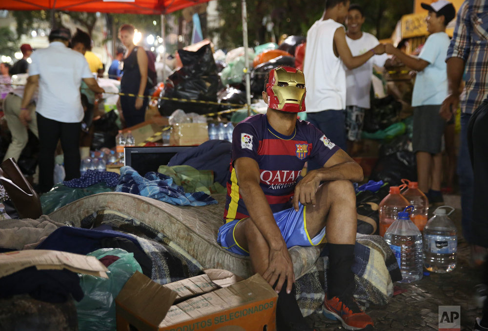 In this May 3, 2018 photo, a masked man sits outside on his belongings after the building he was living in with other squatters burned down, triggered by a short circuit, in downtown Sao Paulo, Brazil. Tens of thousands of working class families in Sao Paulo can't afford to rent an apartment and high transportation costs render low-rent places on the city's outskirts unaffordable. (AP Photo/Andre Penner)