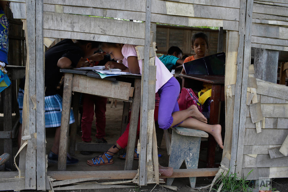 In this May 8, 2018 photo, children study at a run down school in the Amazonian shantytown of Victoria Gracia, Peru. Plant healer of the Shipibo-Konibo tribe, Olivia Arevalo, was allegedly shot to death by a Canadian man in this town. (AP Photo/Martin Mejia)