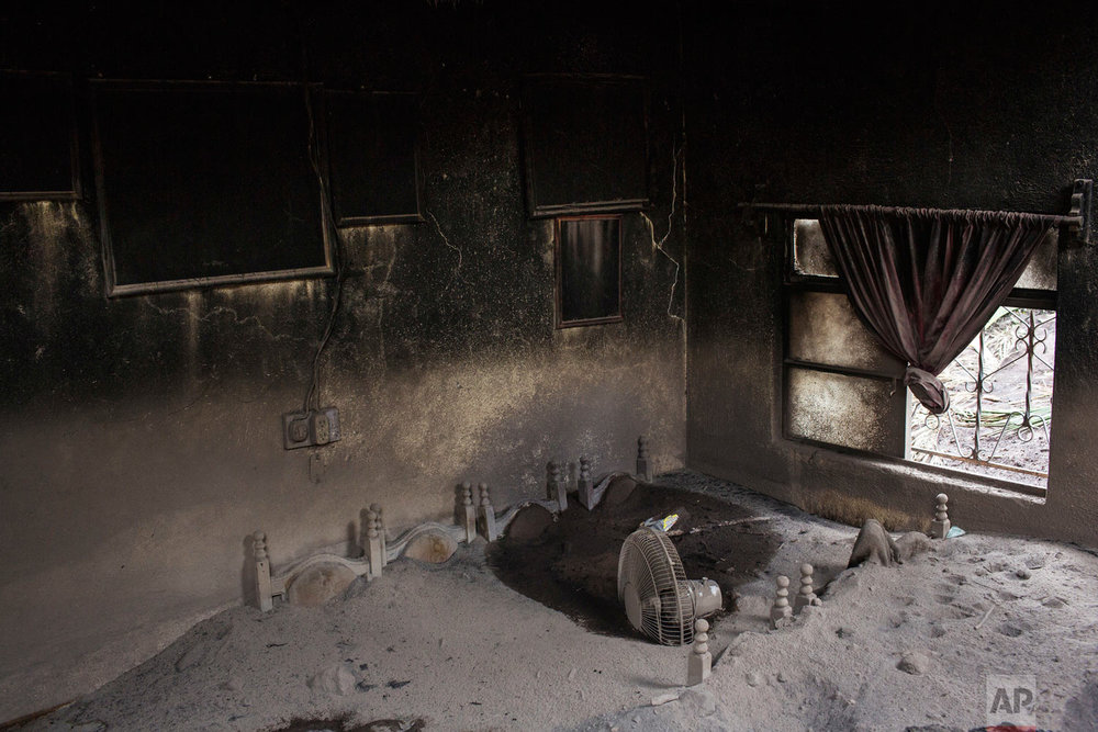In this June 8, 2018 photo, volcanic ash covers a dining room set after the Volcano of Fire erupted in San Miguel Los Lotes, Guatemala. The most active volcano in Central America killed 194 people while another 234 are officially missing. (AP Photo/Rodrigo Abd)