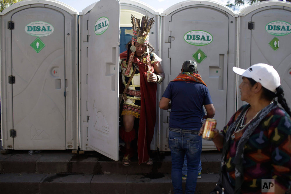 In this June 23, 2018 photo, a man dressed as the Inca Emperor Atahualpa clutches his beer as he leaves a porta-potty in Cuzco, Peru, the day before the Festival of the Sun, or Inti Raymi. (AP Photo/Martin Mejia)