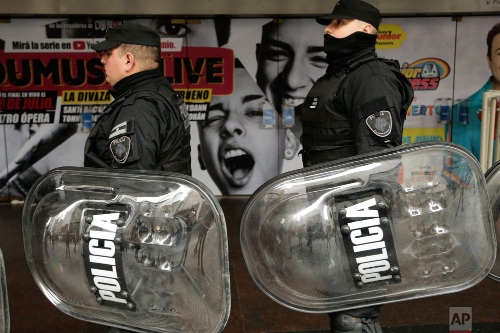 In this July 5, 2018 photo, police carry their shields alongside a march of journalists protesting the layoffs of about 40 percent of the employees from the Telam public news agency in Buenos Aires, Argentina. Argentines have been protesting recent government austerity measures and demanding solutions to the country's economic crisis. (AP Photo/Jorge Saenz)