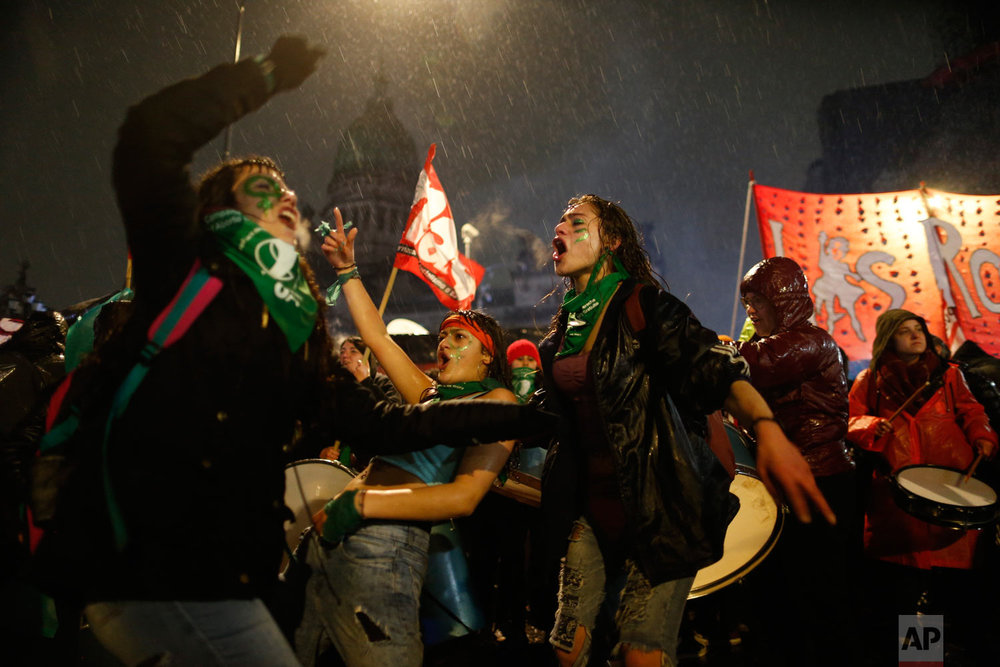 In this Aug. 8, 2018 photo, women who want to decriminalize abortion get soaked as they protest outside Congress where lawmakers are debating the issue in Buenos Aires, Argentina. The Senate decided against legalizing elective abortion in the first 14 weeks of pregnancy. (AP Photo/Natacha Pisarenko)