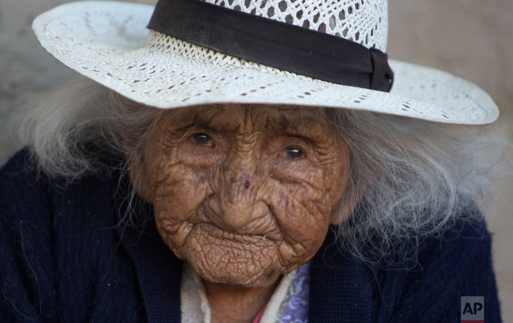 In this Aug. 23, 2018 photo, Julia Flores Colque, born on Oct. 26, 1900 in a mining camp in the Bolivian mountains, looks into the camera outside her home in Sacaba, Bolivia. At age 117, Colque is be the oldest woman in the Andean nation and perhaps the oldest living person in the world. (AP Photo/Juan Karita)