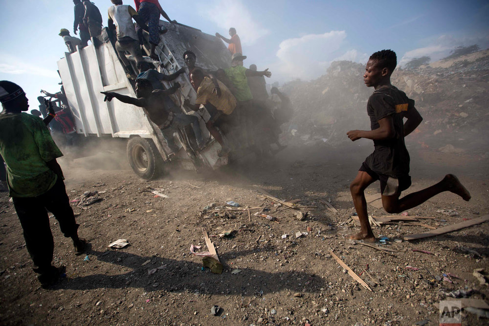 In this Aug. 28, 2018 photo, men who scavenge trash for valuables climb on a trash truck before it unloads at the Truitier landfill in the Cite Soleil slum of Port-au-Prince, Haiti. The landfill, home to about 500 families, is the center of deadly cholera outbreaks when flat lands flood during the rainy season and become a breeding ground for disease-carrying mosquitoes. (AP Photo/Dieu Nalio Chery)