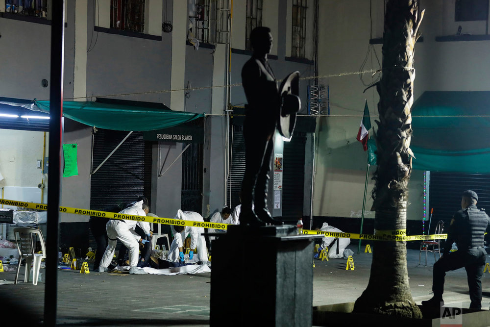 In this Sept. 14, 2018 photo, crime scene workers cover the bodies of four people who were shot to death in Garibaldi Plaza in Mexico City. Homicides in Mexico rose by 16 percent in the first half of 2018, as the country again broke its own records for violence. (AP Photo)