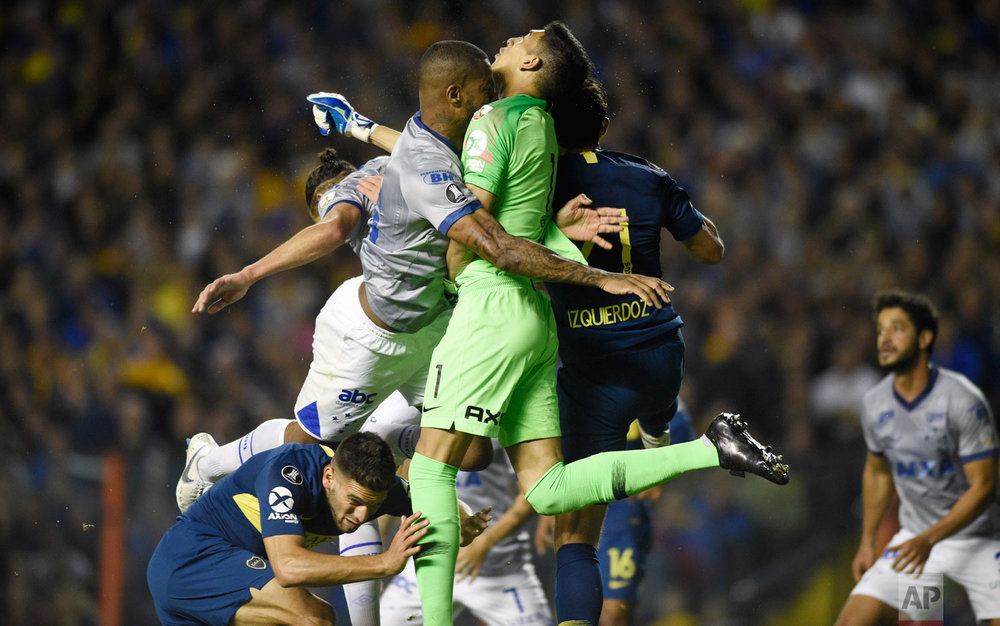 In this Sept. 19, 2018 photo, Dede of Brazil's Cruzeiro, left, and goalkeeper Esteban Andrada, of Argentina's Boca Juniors, collide during a Copa Libertadores soccer match in Buenos Aires, Argentina. (AP Photo/Gustavo Garello)