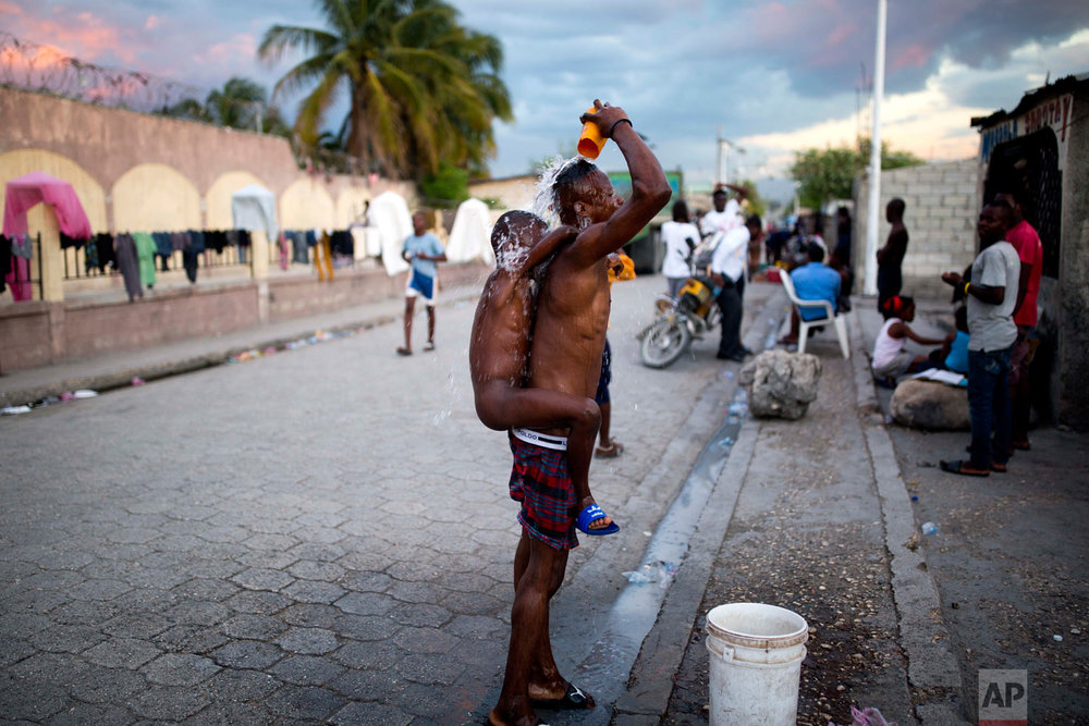 In this Nov. 13, 2018 photo, a man takes a public bucket shower with his nephew on his back in the Cite Soleil slum of Port-au-Prince, Haiti. Most residents in Cite Soleil do not have bathrooms, and bathe outdoors. (AP Photo/Dieu Nalio Chery)