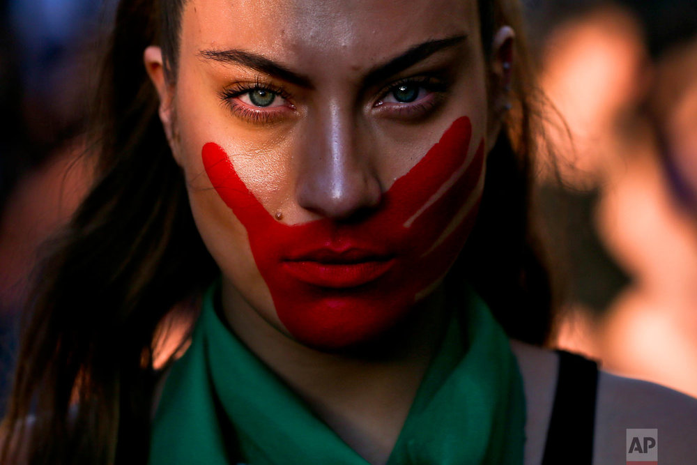 In this Nov. 22, 2018 photo, a woman joins a march against sexism and gender violence in Santiago, Chile. (AP Photo/Esteban Felix)