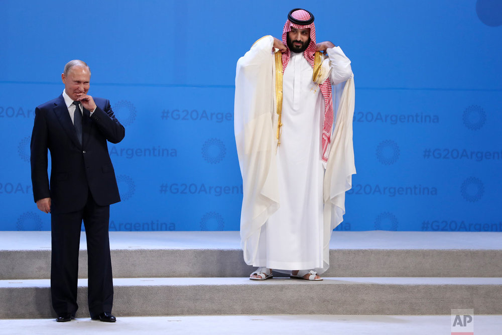 In this Nov. 30, 2018 photo, Russia's President Vladimir Putin and Saudi Arabia's Crown Prince Mohammed bin Salman wait for  the G20 group photo in Buenos Aires, Argentina. All eyes were on the Saudi Crown Prince at the Group of 20 summit as he made his first major overseas appearance since the killing of a dissident journalist in his country's consulate in Istanbul. (AP Photo/Ricardo Mazalan)