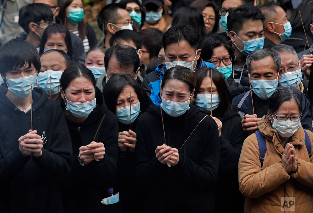 Relatives pay last tributes to victims of a bus crash in Hong Kong on Feb. 11, 2018. (AP Photo/Vincent Yu)