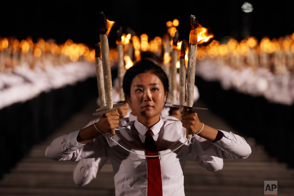 North Korean youths hold torches during a torch light march at the Kim Il Sung Square in conjunction with the 70th anniversary of North Korea's founding day in Pyongyang, North Korea, on Sept. 10, 2018. (AP Photo/Kin Cheung)